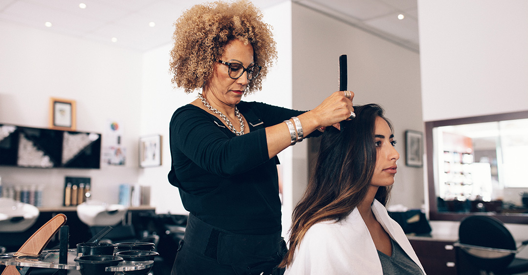 Photo of Woman hairdresser at work in salon illustrating hairdressing industry