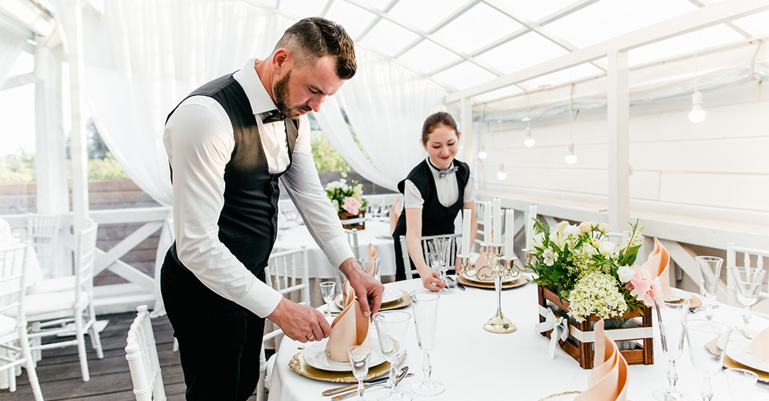 Photo of Two male and female waiters serve a table in the restaurant wiping glasses for wine illustrating hospitality industry