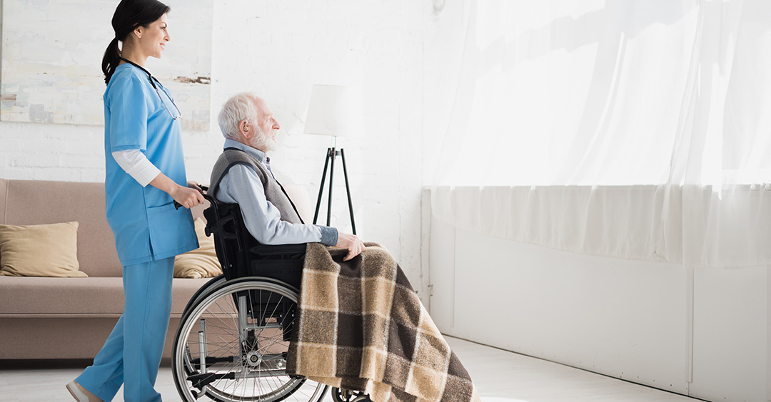 Photo of Side view of happy nurse standing in room with copy space, and carrying about disabled grey haired man in wheelchair illustrating retirement and care homes